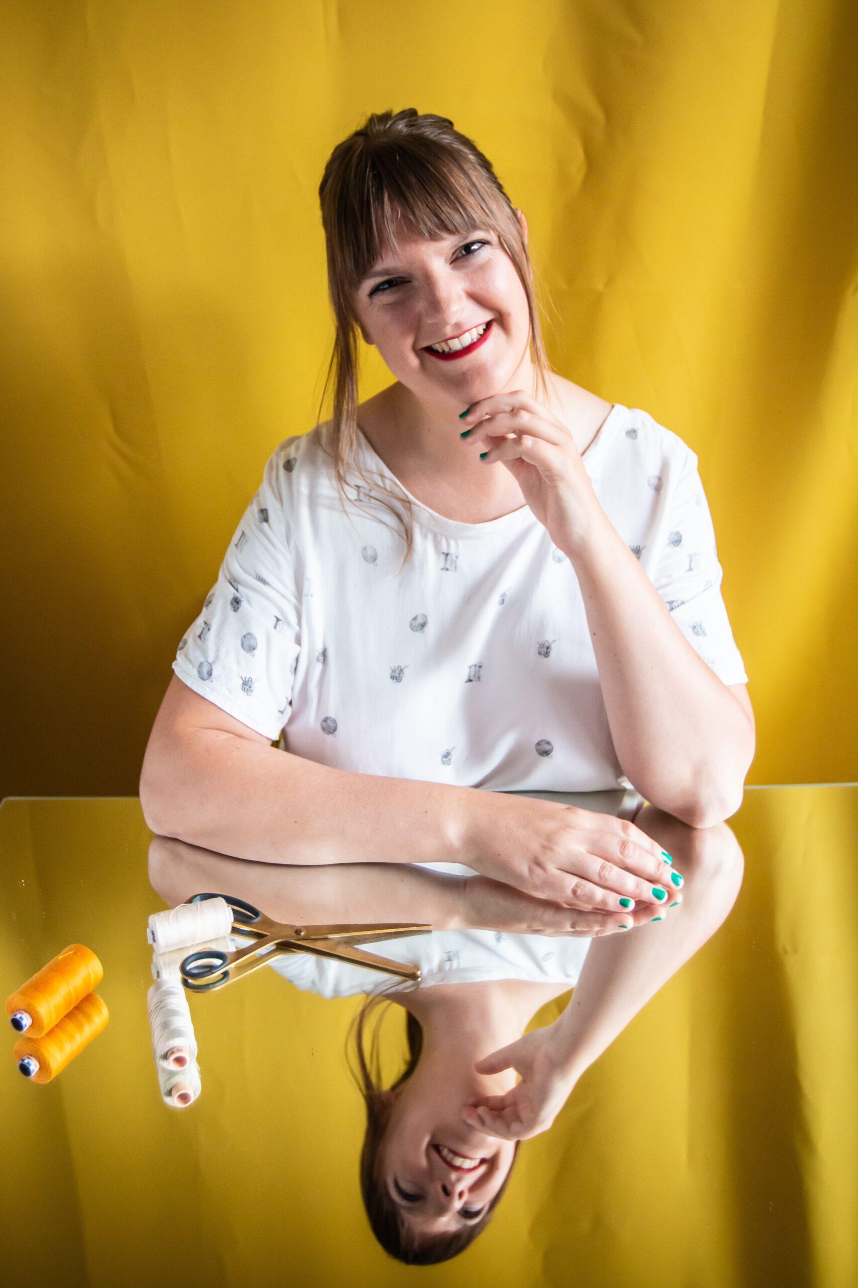 Tine Sews - Frau sitzt vor einem gelben Hintergrund und auf einem Spiegel vor ihr liegen Nähutensilien