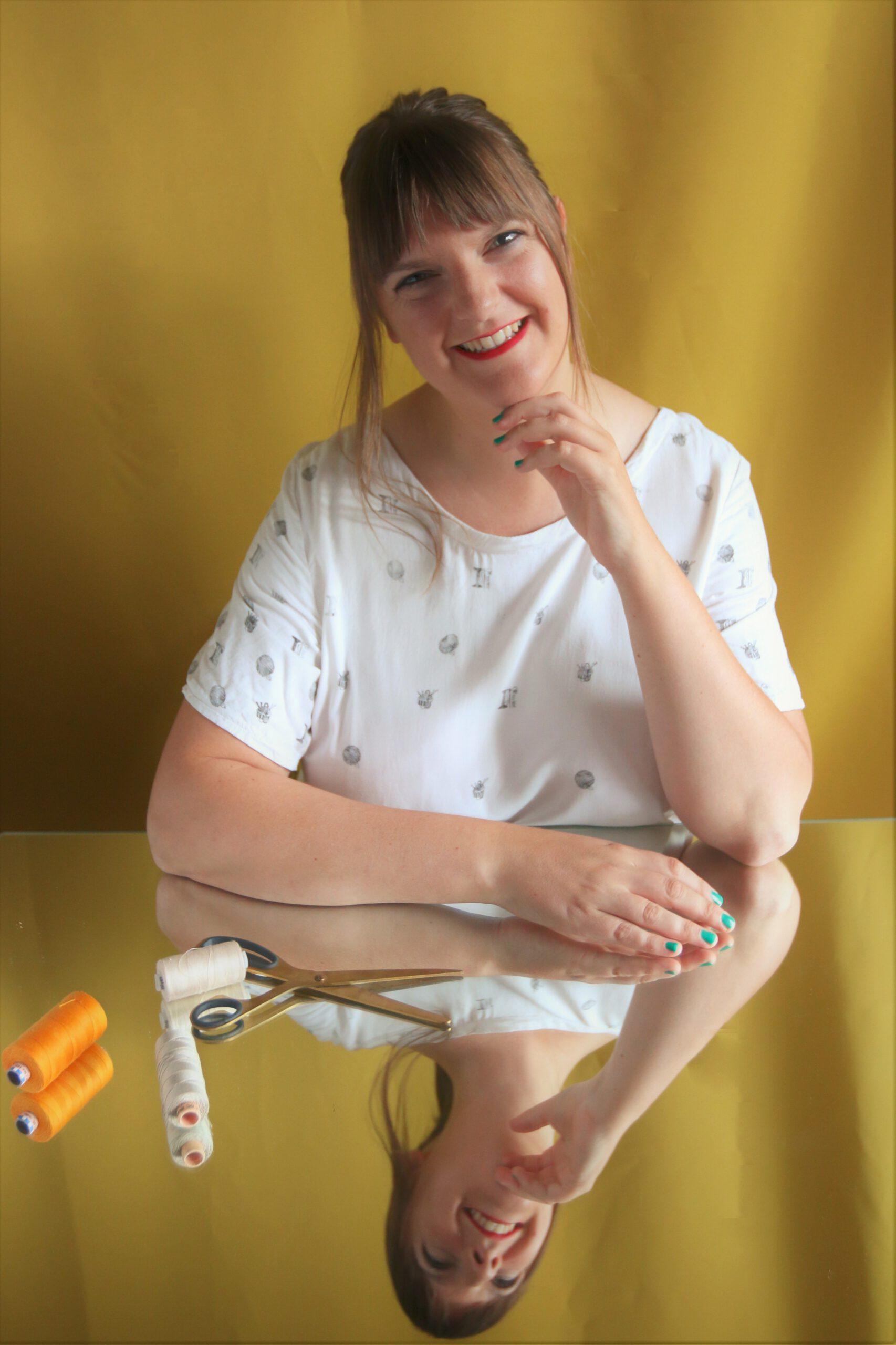 Tine vom Nähblog Tine Sews sitzt an einem Tisch und vor ihr liegen Nähutensilien wie Garn und Schere